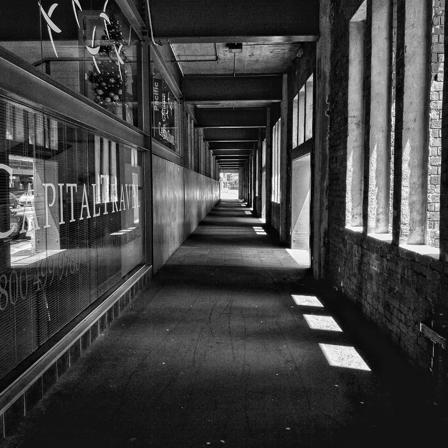 Black and white picture of a corridor sidewalk with decrepit walls on the right and under construction shops on the left